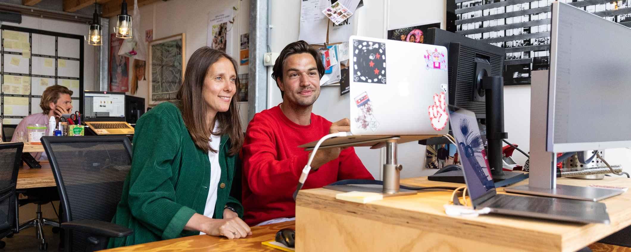 Twee medewerkers van het Volkshotel aan het werk achter laptop - Triodos Bank