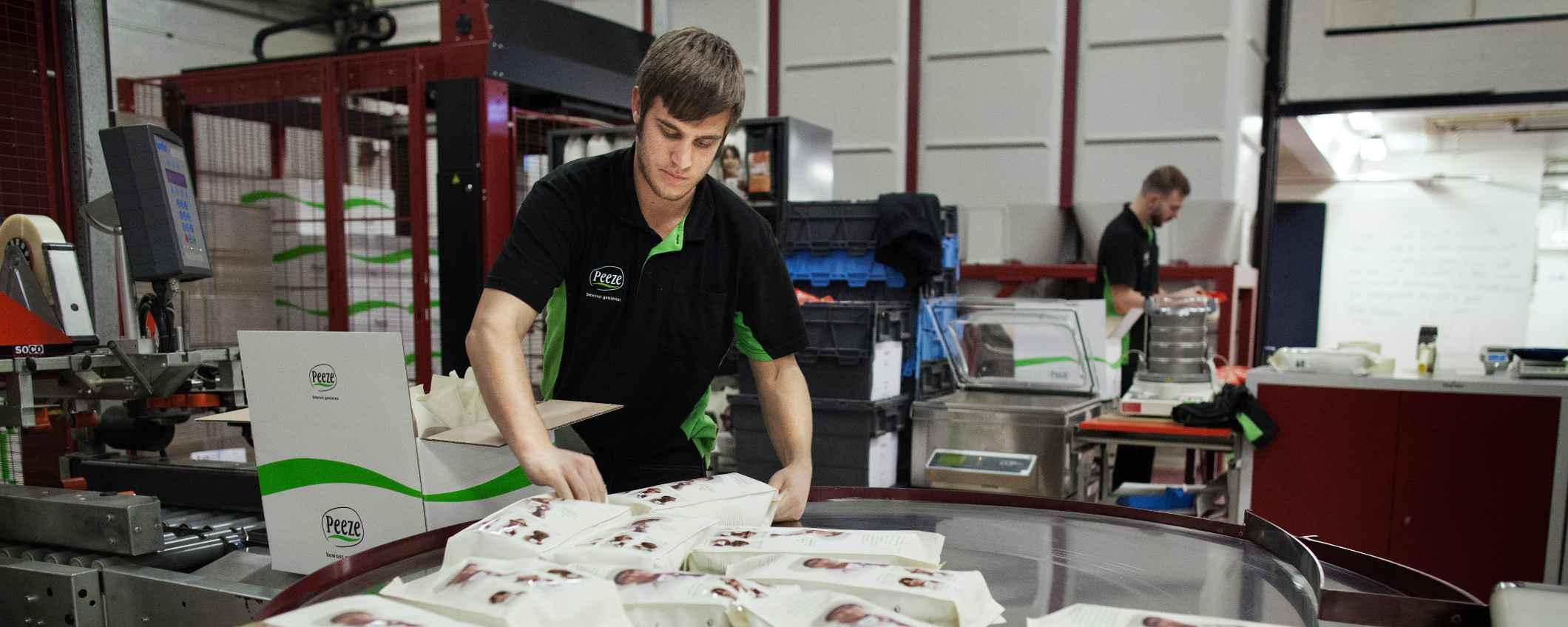 Medewerker koffiemaker Peeze verpakt composteerbare koffieverpakking
